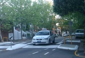 Taxi crossing elevated pedestrian crosswalk